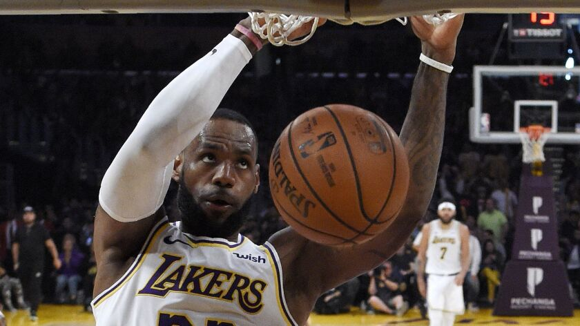 Lakers forward LeBron James dunks during the second half of the game against the Magic on Sunday.