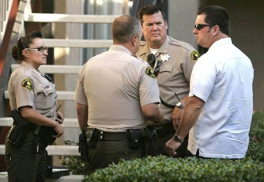 San Diego County Sheriff's deputies confer at the scene where a man was shot in the face on Mapleview Street in Lakeside last month. The county paid its employees $2.1 million in uniform allowances last year, which count toward pension calculations.