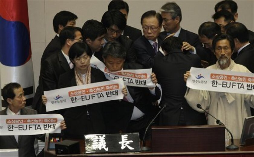 National Assembly Speaker Park Hee-tae, top center, is surrounded by parliament officials as he attempts to sit his seat in a session to pass a bill to ratify the free trade agreement (FTA) with the European Union (EU) at the National Assembly in Seoul, South Korea, May 4, 2011. Labor Party lawmake