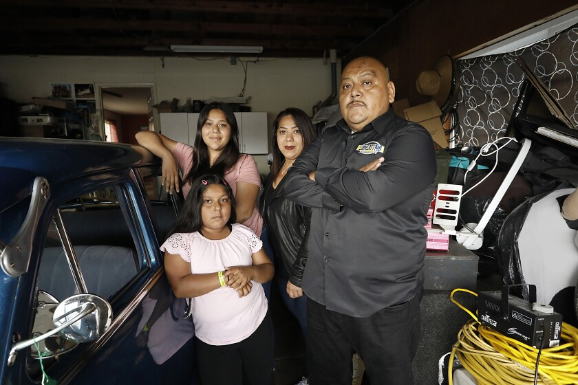 Juan Lira stands with his family in their Otay Mesa garage where has had to store his DJ gear since COVID-19.