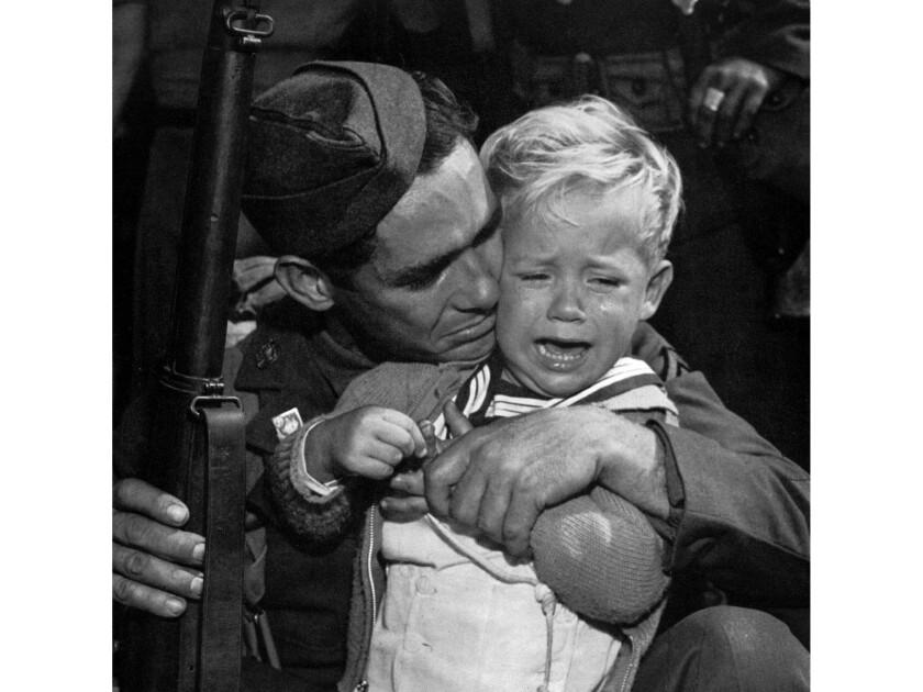 Oct. 31, 1940: Private John G. Winbury gives a hug to his son Robert Austin Winbury, 2, as he prepar