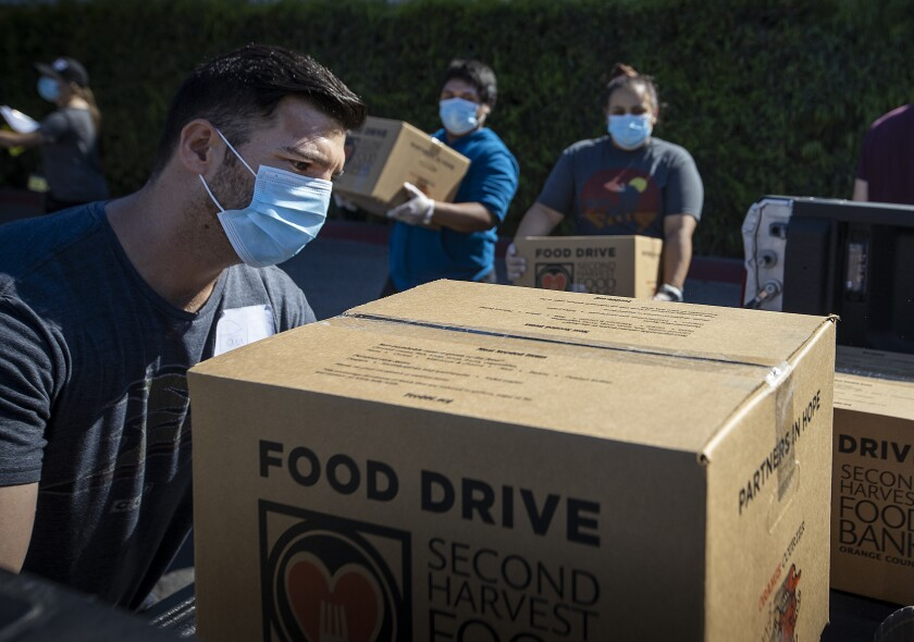 People load boxes of food into trucks to be delivered to Orange County senior centers