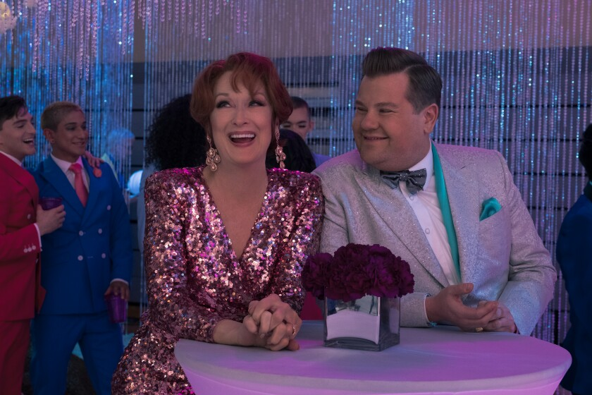 """Meryl Streep wears a glittery gown and earrings and James Corden wears a glittery silver tux in a scene from """"The Prom."""""""