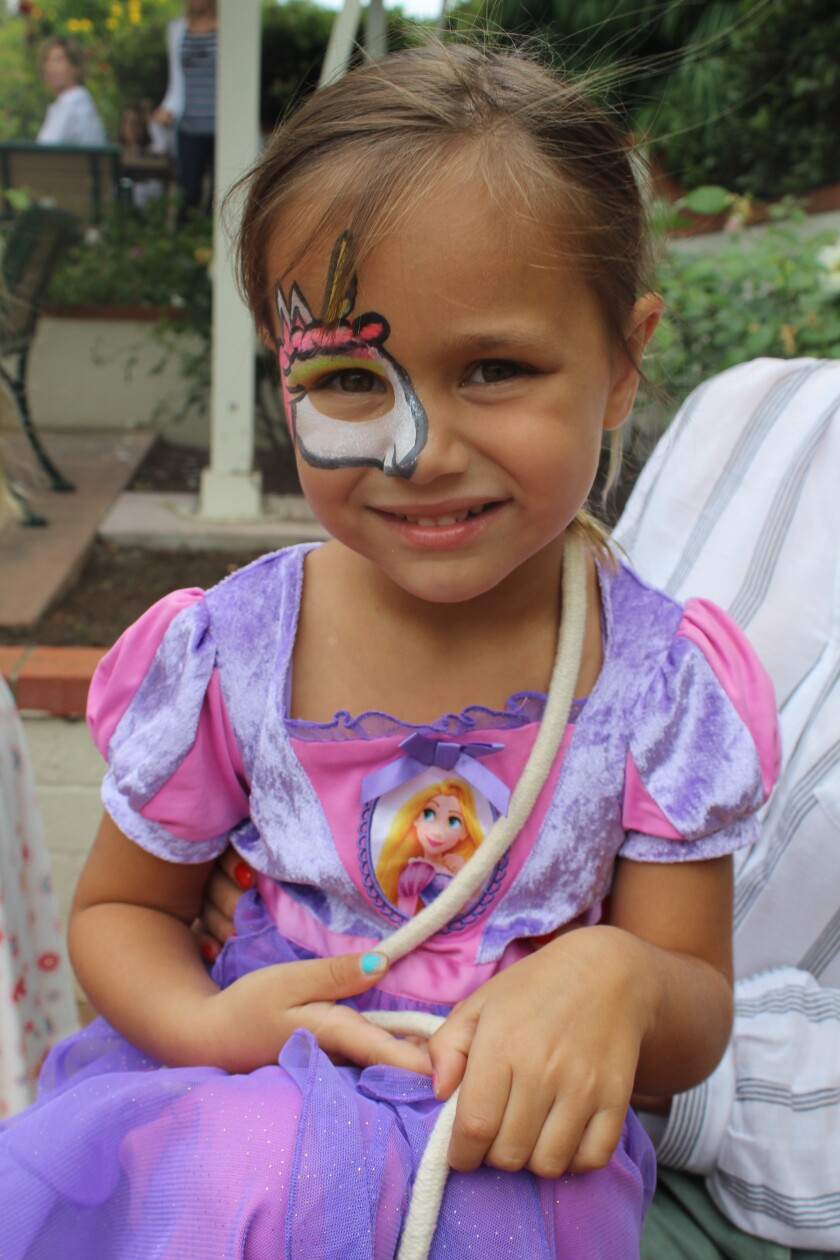 Lily AKA Rapunzel shows off her unicorn face paint.