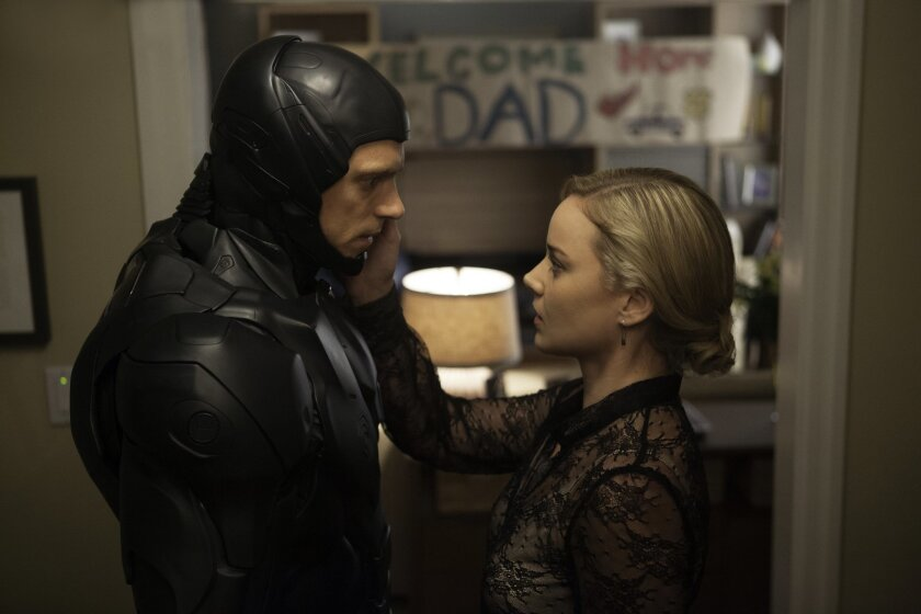 """This image released by Columbia Pictures shows Joel Kinnaman, left, and Abbie Cornish in """"Robocop."""" (AP Photo/Sony, Columbia Pictures, Kerry Hayes)"""