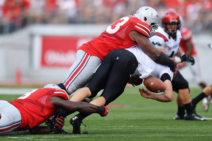 Michael Bennett #63 of the Ohio State Buckeyes sacks quarterback Quinn Kaehler #18 of the San Diego State Aztecs and causes a fumble in the second quarter that Bennett recovered.