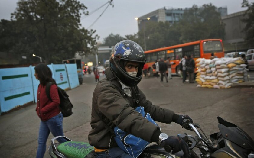 An Indian man riding his motorcycle covers his face from smog in New Delhi. During his visit this week to the Indian capital, President Obama will breath some of the world's dirtiest air.