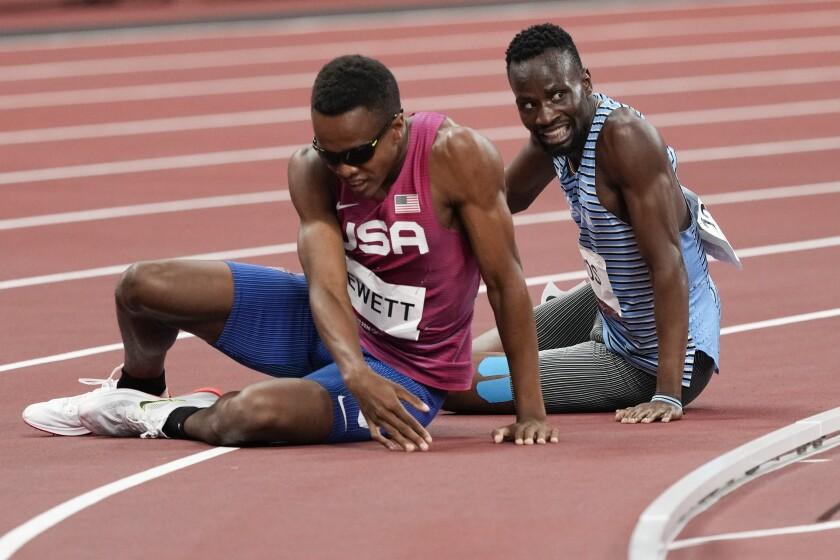 U.S. runner Isaiah Jewett and Nijel Amos of Botswana sit on the track.