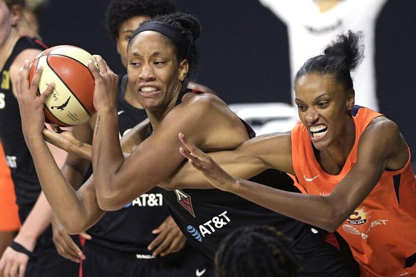 Las Vegas Aces center A'ja Wilson grabs a rebound away from Connecticut Sun forward DeWanna Bonner.