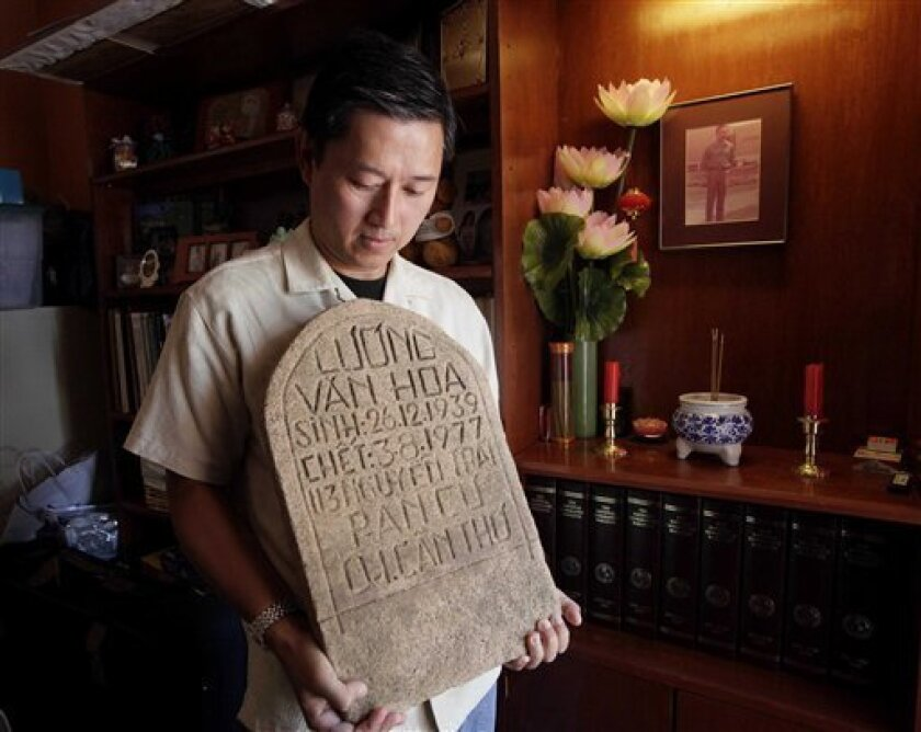 In this photo taken Friday, July 29, 2011, Daniel Luong holds the tombstone of his father, former South Vietnamese Army Capt. Luong Van Hoa, at his home in Los Angeles. Nearly a year to the day after collecting the tombstone and human remains from a grave at the former site of the Lang Da re-educat