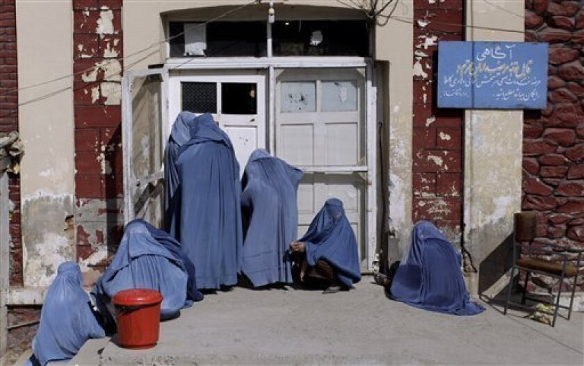 FILE - In this Wednesday, Oct. 26, 2011 file photo, an Afghan woman, center, peeks inside a hospital while she and others wait for an employee to let them enter, on the outskirts of Kabul, Afghanistan. An Afghan woman has been strangled to death, apparently by her husband, who was upset that she ga