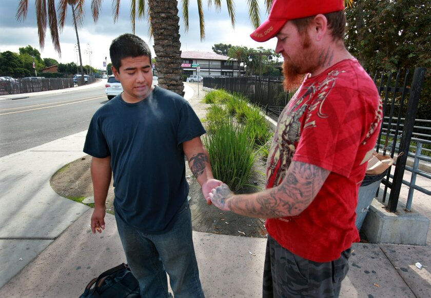 Former Marine Joshua Lopez (left) a veteran of the 1st battalion, 5th regiment, spends most of his time now smoking cigarettes with friends near MCRD and looking for work. Peggy Peattie • U-T photos