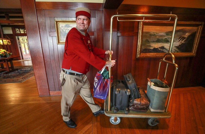 Bellman Justin Davis pushes a cart holding the luggage of a couple from San Diego who are staying at The Lodge at Torrey Pines in La Jolla while their home is being fumigated.
