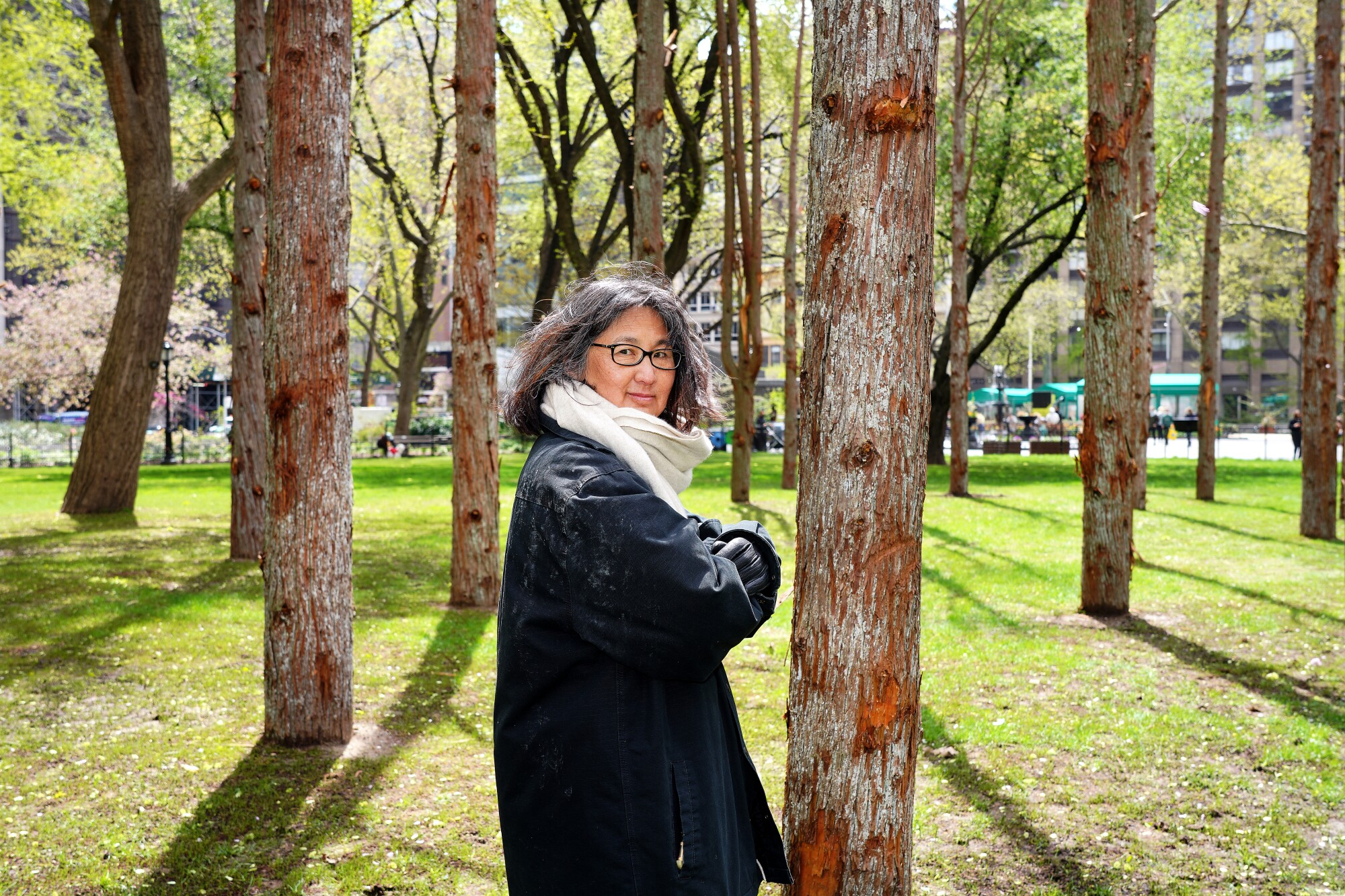 """Maya Lin, in a black coat, stands amid the dead tree trunks of her """"Ghost Forest"""" installation."""
