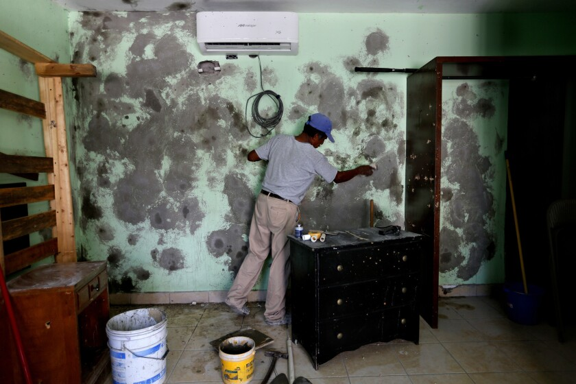 A worker spackles the walls after a deadly shootout in Los Cabos, Mexico, in 2017.