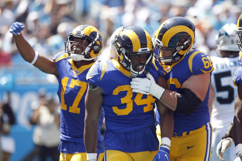 Rams running back Malcolm Brown (34) is congratulated by center Austin Blythe (66) and wide receiver Robert Woods (17) following Brown's touchdown against the Carolina Panthers during a September game last season in Charlotte.