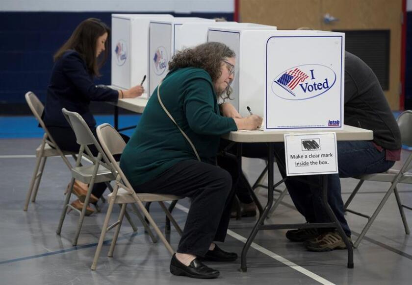 Votantes rellenan sus papeletas antes de ejercer su derecho al voto. EFE/Archivo