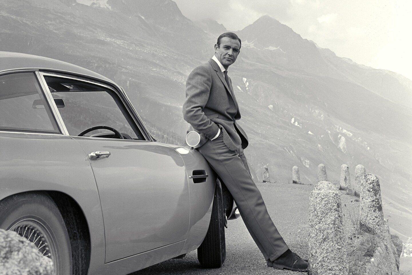 Sean Connery poses with his signature Aston Martin in the 1964 movie Goldfinger.