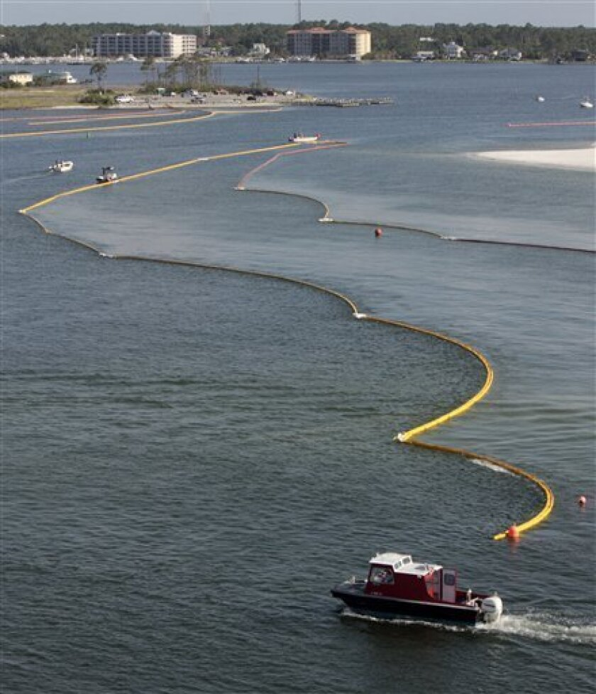 Boats work to secure oil containment booms in the Perdido Pass in Orange Beach, Ala., Friday, June 4, 2010. Oil from the Deepwater Horizon disaster has started washing ashore on Alabama and Florida coast beaches. (AP Photo/Dave Martin)
