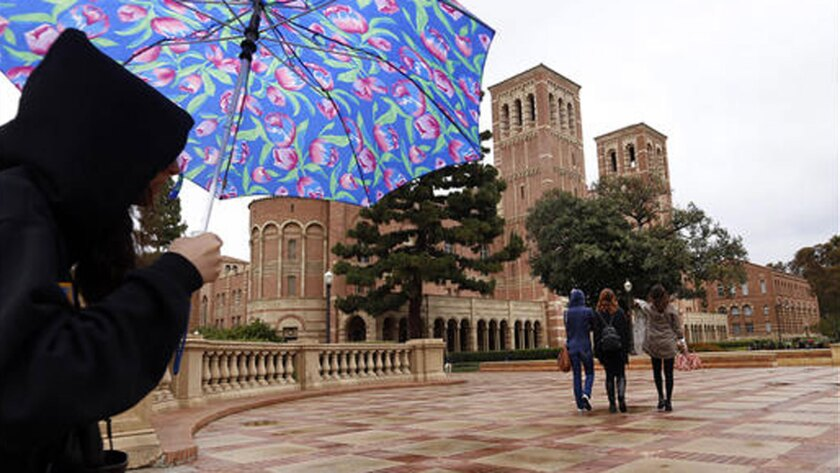 Students walk in the rain last month near Royce Hall on the UCLA campus.