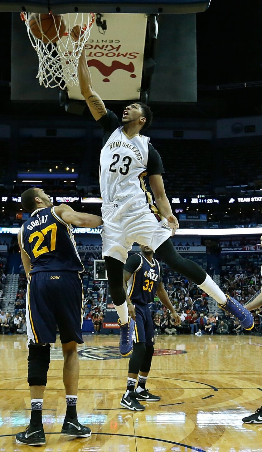 New Orleans Pelicans forward Anthony Davis (23) dunks over Utah Jazz center Rudy Gobert (27) during the second half of an NBA basketball game in New Orleans, Wednesday, Feb. 10, 2016. The Pelicans won 100-96. (AP Photo/Tyler Kaufman)