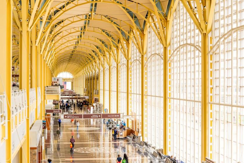 Passengers walking through a bright airport