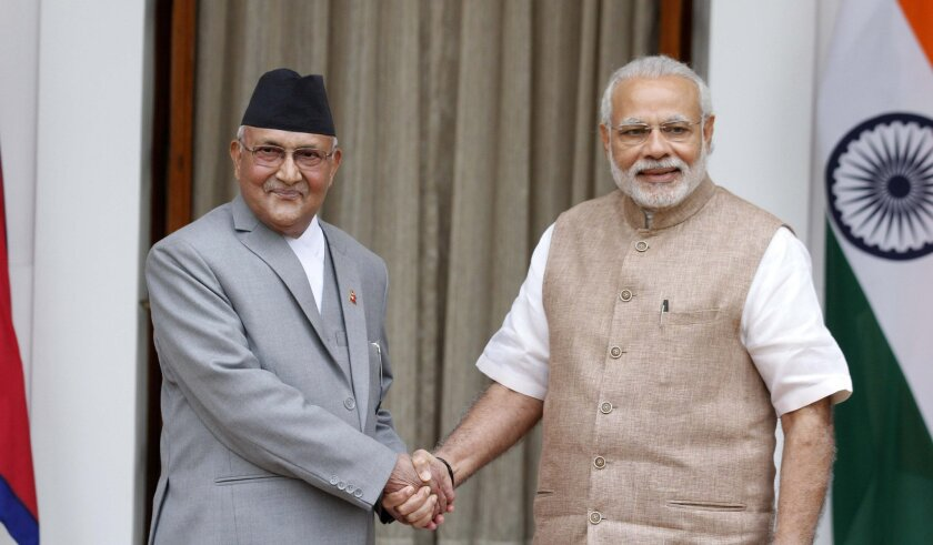 Nepalese Prime Minister Khadga Prasad Oli, left, poses with Indian Prime Minister Narendra Modi before their meeting in New Delhi, India, Saturday, Feb. 20, 2016. India has pledged $250 million for post-earthquake reconstruction in Nepal as the two countries try to remove irritants in their ties following protests in Nepal over the country's new constitution.(AP Photo) NO ARCHIVE, NO LICENSING