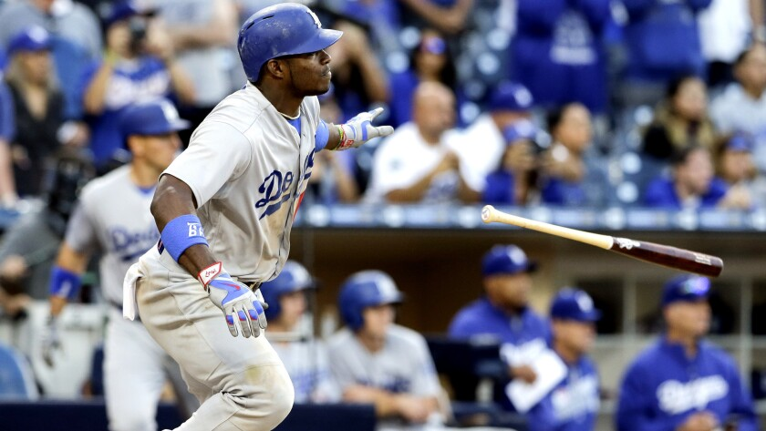 Dodgers right fielder Yasiel Puig flips his bat aside as he watches his two-run single against the Padres in the 17th inning Sunday.