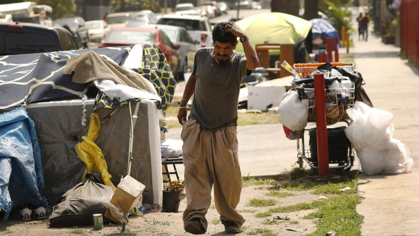 Pablo Rivera Gomez walks outside his tent last year. It was one of several at a sidewalk encampment on Leeward Avenue, close to a site in L.A.'s Koreatown that had been under consideration for a homeless shelter.