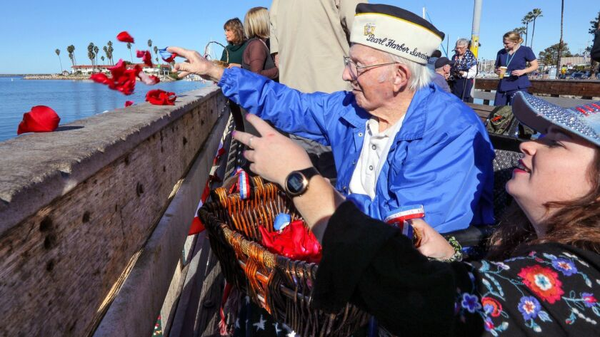 At the Pearl Harbor Memorial event at the Oceanside Harbor 98 year old Pearl Harbor survivor John Quier and his great grand daughter Melissa Sterling, 24, toss rose petals in the water in memory of
