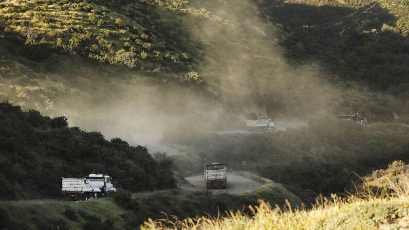 CHATSWORTH, CA – APRIL 24, 2018: Trucks rumble down the dirt road onto Wayne Fishback's ranch in