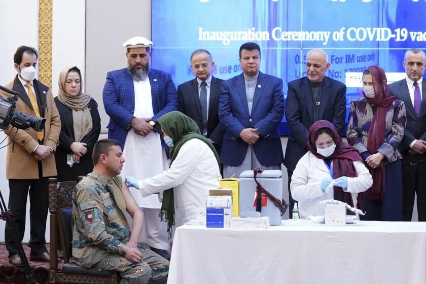 Un miembro de las fuerzas de seguridad afganas (izquierda), recibe una dosis de la vacuna de AstraZeneca-
