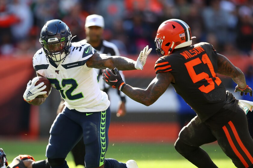 Seattle Seahawks running back Chris Carson, left, battles for yards against Cleveland Browns linebacker Mack Wilson during the fourth quarter of Sunday's game.