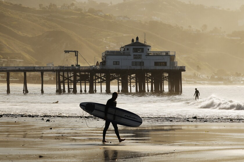 MALIBU, CA - MAY 13: Surfers take advantage of the low tide swell at Malibu Surfrider Beach next to the Malibu Pier Wednesday morning as Los Angeles County Beaches reopened for active use only. The beaches have been closed for two months due to the coronavirus Covid-19 pandemic and remained off limits even as the coastline reopened for active use in Orange County. Beachgoers will have to wear masks and maintain a six-foot buffer between themselves and others under continued social distancing requirements. Parking lots, piers and boardwalks will remain closed. Malibu Pier on Wednesday, May 13, 2020 in Malibu, CA. (Al Seib / Los Angeles Times)