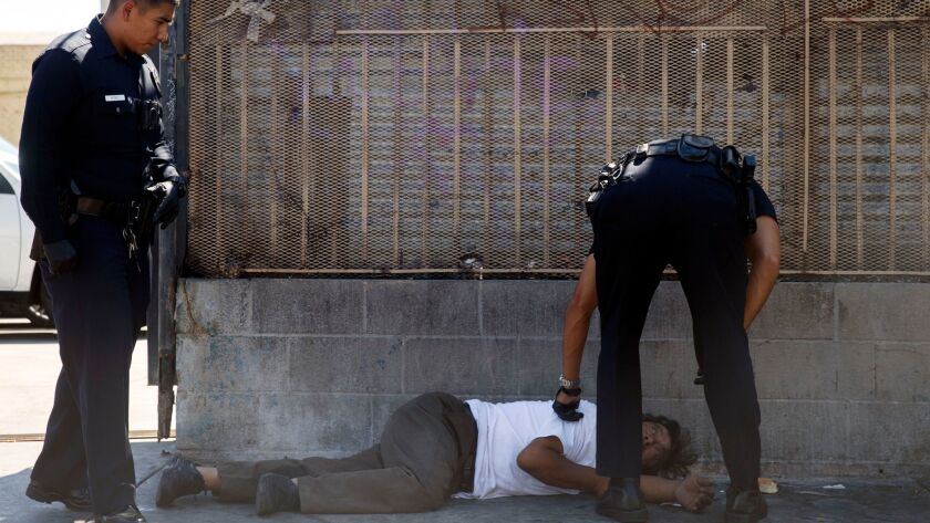 LAPD officers tend to a person who has fallen ill on skid row in August 2016.