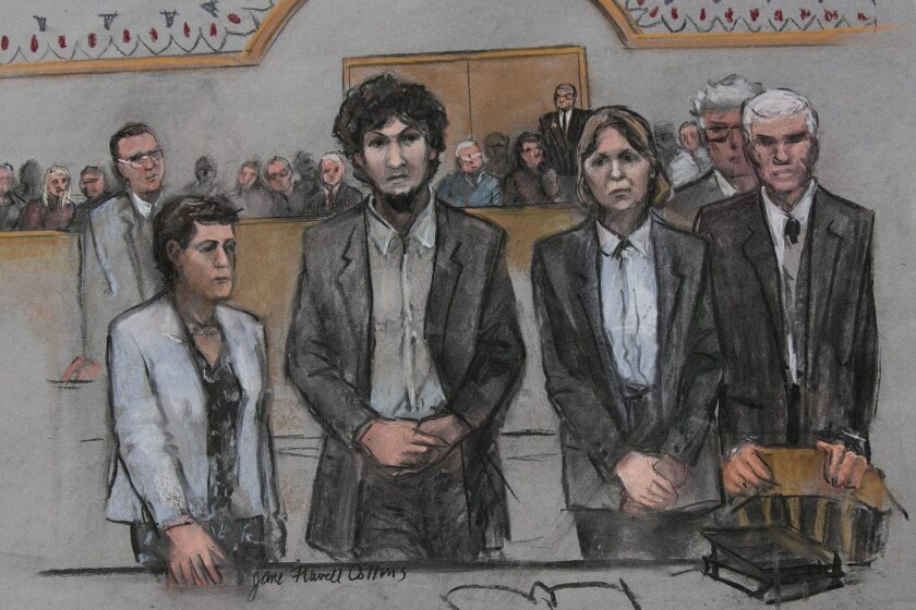 In this courtroom sketch, convicted Boston Marathon bomber Dzokhar Tsarnaev, center, stands with his defense team as he is sentenced to death.