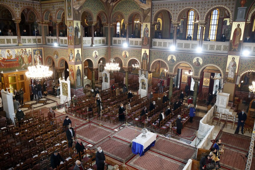 A limited congregation attends the service for the feast of the Epiphany in the Church of the Holy Trinity in Piraeus, the port of Athens, Wednesday, Jan. 6, 2021. The Greek government relented and allowed limited attendance at churches celebrating the feast of the Epiphany on Wednesday, reversing a ban on attendance designed to limit the spread of the coronavirus. (AP Photo/Thanassis Stavrakis)