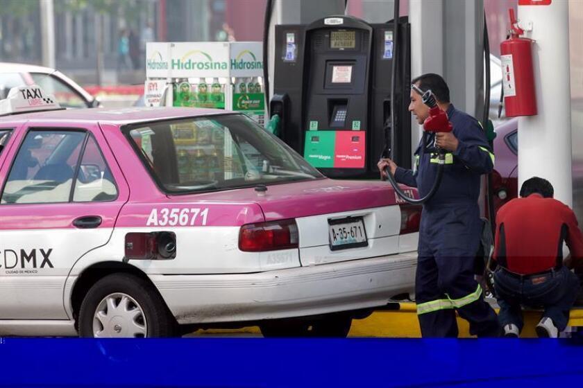 Un hombre trabaja en una estación de gasolina hoy, 27 de diciembre de 2016, en Ciudad de México. El Gobierno de México informó hoy que el precio de las gasolinas subirán en el país entre el 14 % y el 20 % en enero de 2017, un alza anticipada hace unos días por la estatal Petróleos Mexicanos (Pemex) y que llega antes de la liberalización de los precios del sector, que comenzará en marzo. EFE