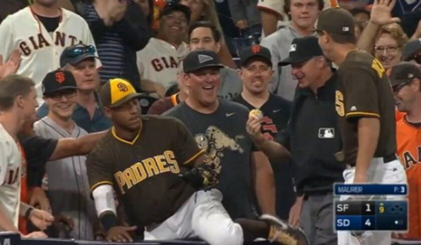 Third base umpire Ed Hickox examines glob of nacho cheese on the baseball after taking ball out of Padres third baseman Yangervis Solarte's glove. Solarte tumbled into the stands in the ninth inning of Friday night's game against the Giants to make an outstanding catch.