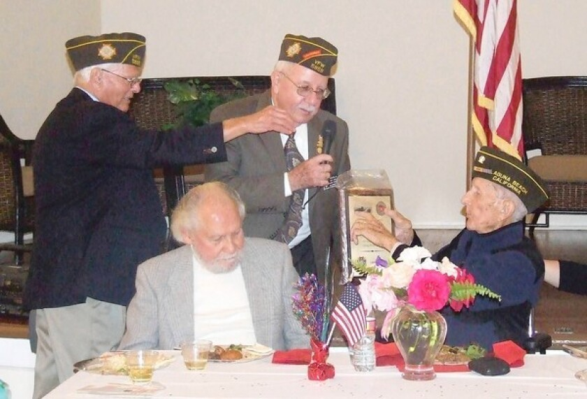 Commander Bill Sandlin presents a plaque to Harry Lawrence at the VFW Post 5868 dinner.