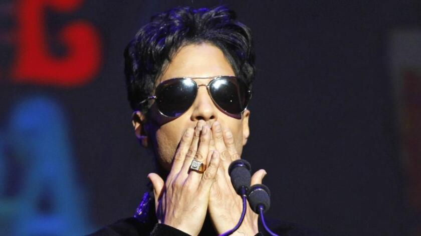 """Singer Prince gestures as he announces upcoming live dates at the Apollo Theater in New York October 14, 2010. U.S. pop star Prince, the 57-year-old whose hits included """"Purple Rain"""" and """"Kiss,"""" was found unresponsive on Thursday at his Minnesota home and was later declared dead, U.S. media reports said. (LUCAS JACKSON / Reuters Photo)"""
