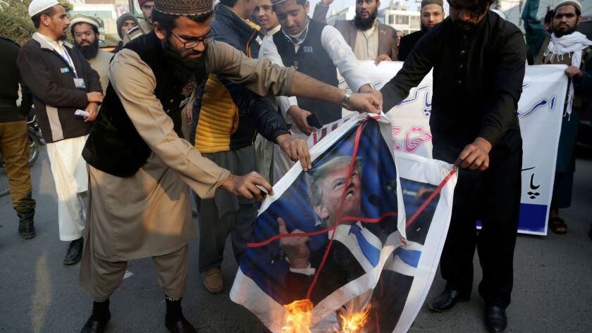 Protesters burn posters of President Trump in Lahore, Pakistan, on Friday.