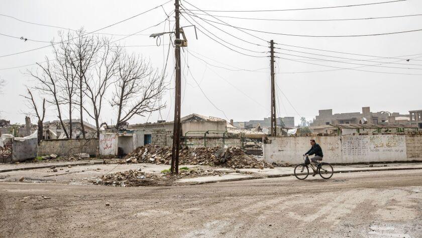 A man bicycles through west Mosul, Iraq.