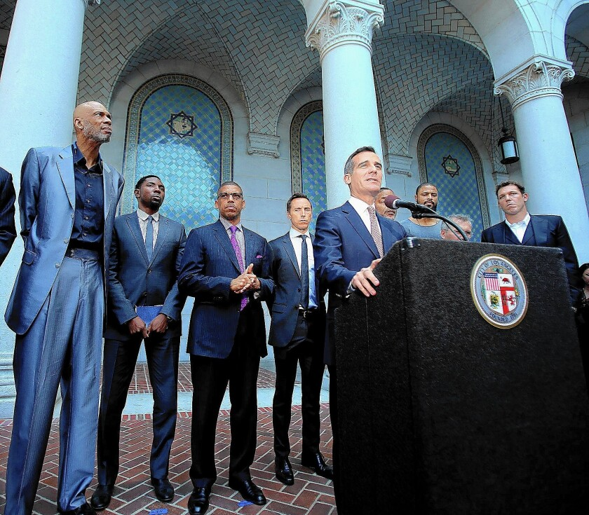 L.A. Mayor Eric Garcetti, flanked by former and current professional basketball players, holds a news conference on the steps of City Hall to talk about the lifetime ban imposed by the NBA on L.A. Clippers owner Donald Sterling.