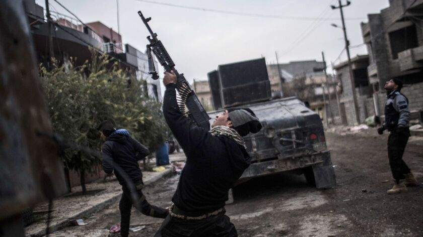 A member of the Iraqi Special Forces shoots his machine gun at an Islamic State militant drone in th