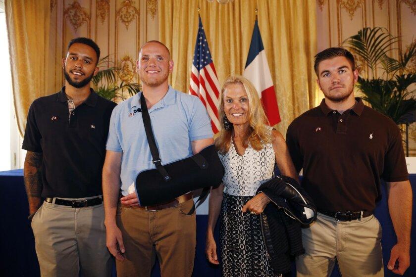 From left, Cal State Sacramento student Anthony Sadler, U.S. serviceman Spencer Stone, U.S. ambassador to France Jane Hartley and National Guardsman Alek Skarlatos pose after a news conference at the U.S. Embassy in Paris on Sunday.