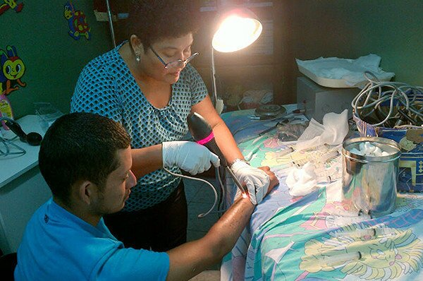 Veteran nurse Suyapa Bonilla directs infrared light onto the tattooed forearm of Osman Torres in her clinic in San Pedro Sula, Honduras. Rising gang violence has led her to limit the number of patients she sees.