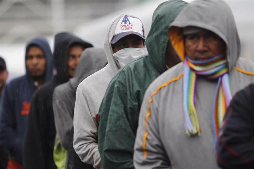 """Migrantes centroamericanos se protegen del frio debido a una onda gélida que afecta al país hoy, miércoles 14 de noviembre de 2018, mientras permanecen en el estadio deportivo Jesús Martínez """"Palillo , en Ciudad de México (México). EFE"""
