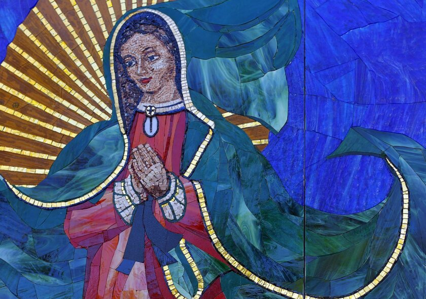 Artist Mark Patterson installed the Surfing Madonna on a wall next to Surfy Surfy surf shop on North Coast Highway in Leucadia on Monday, June 25, 2012. The mosaic is made mostly of glass and stones.