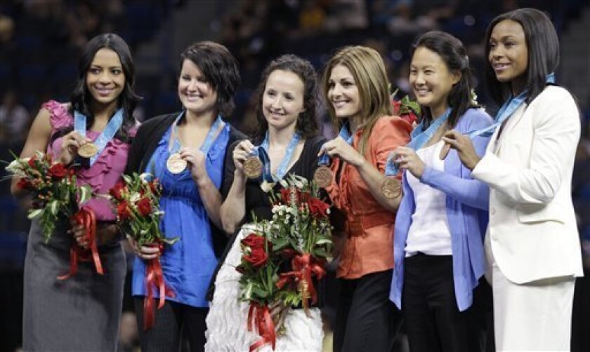 United States' gymnasts from the 2000 Sydney Olympics hold up their bronze medals following a ceremony in Hartford, Conn., Wednesday, Aug. 11, 2010. The U.S. women's team received the third-place medals that were stripped from China because a member of that team was found to be underage. From left to right, are: Tasha Schwikert, Elise Ray, Kristin Maloney, Jamie Dantzscher, Amy Chow and Dominique Dawes. (AP Photo/Charles Krupa)